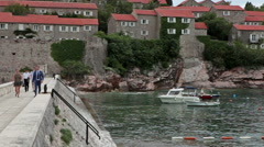 Guests walk to mainland by a narrow isthmus from the Sveti Stefan spa entrance Stock Footage