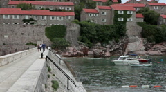 People walk to mainland by a narrow isthmus from the Sveti Stefan hotel entrance Stock Footage