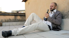 Man alone lying on the ground gets drunk with wine bottle Stock Footage