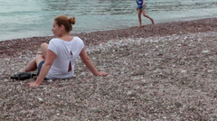 Woman sitting on the luxury beach against Sveti Stefan hotel and resort Stock Footage