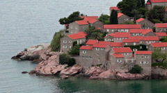 Red roof houses are built on the rocky island of Sveti Stefan. Montenegro Stock Footage