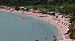 Top view at the sandy Jaz beach with sunbeds and parasols and azure Adriatic sea Stock Footage
