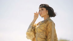 Beautiful woman with fashion make-up and hairstyle like Egyptian queen Cleopatra Stock Footage