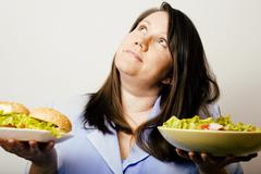 Fat white woman having choice between hamburger and salad close Stock Photos