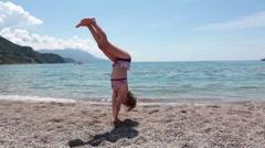 Pretty Caucasian girl shows gymnastic exercises cartwheel on a sandy beach Stock Footage