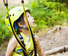 Little cute boy in helmet runs track in green forest, happy smiling brave kid Stock Photos