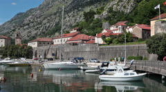 Yachts mooring place is near road passing along walls of old town of Kotor Stock Footage