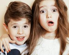 Little cute boy and girl hugging playing on white background, happy family Stock Photos