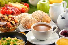 Breakfast served with coffee, orange juice, egg, rolls and honey. Balanced di Stock Photos