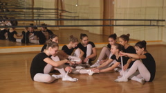 Group of eight little ballerinas sitting on the floor Stock Footage