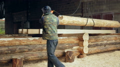 Builder raises wooden timber with Overhead Winch Crane. A man holds a log and Stock Footage