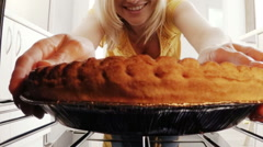 Young woman putting a baking pan with sweet food to bake in oven Stock Footage