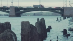 Wooden logs sticking out water near stone embankment city bridge on background Stock Footage