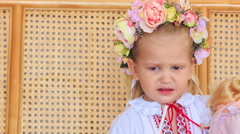 Closeup Little Blond Girl in Garland Chews Candy Stock Footage