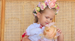 Closeup Little Blond Girl in Garland Sits with Doll Stock Footage