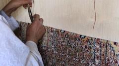 Carpet weaving. Man weaves a carpet Kashmir at weaving factory. Srinagar, India Stock Footage
