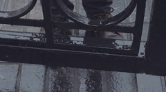 Close up foots in shoes of young man who standing near iron gates under rain Stock Footage