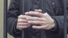 Young man hand gripping iron bars close up Stock Footage