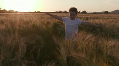 Slow motion view of cute boy running through a wheat field, backlit at sunset Stock Footage