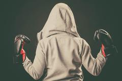 Boxer in hoodie stand backwards with arms in air. Stock Photos
