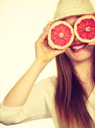 Woman holds two halfs of grapefruit citrus fruit in hands Stock Photos