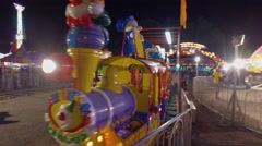 Fall Fair Medium shot follows a carnival train ride go around on it's tracks Stock Footage