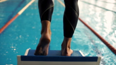 Professional concentrated male swimmer on starting block. Jump into water. Stock Footage