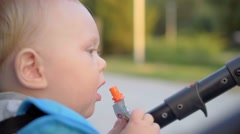 Baby sitting in a pram and eating a bag with baby food Stock Footage