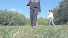 Barefoot man walking on glade with woman Stock Footage