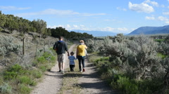 Young family and dog walk away down sagebrush-lined country lane Stock Footage