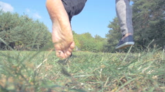 Barefoot man running on glade with woman and holding her hand Stock Footage