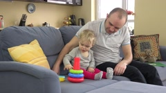 Lovely girl and loving father play colorful pyramid rings. Man commend daughter Stock Footage
