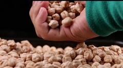 Chickpeas taken by woman hand isolated in black background Stock Footage