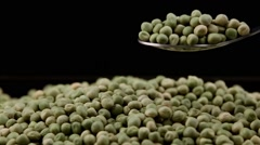 Green peas taken with metal spoon isolated in black background Stock Footage