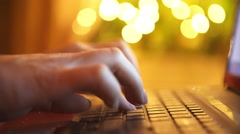 Woman's hand typing on laptop keyboard. Garlands on a background Stock Footage