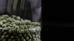 Green peas falling isolated in black background in a jar Stock Footage