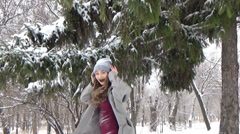 Girl shakes off snow with spruce. Stock Footage