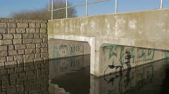 Dappled light reflects off water onto concrete bridge with graffiti Stock Footage