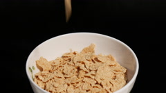 Falling corn flakes to the rotating white plate on a black Stock Footage