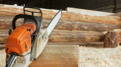 Chainsaw builder at the site of construction of a wooden house. Many sawdust and Stock Footage