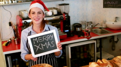 Portrait of waitress showing chalkboard with merry x-mas sign Stock Footage