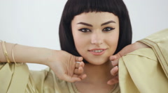Smiling girl with Cleopatra's make-up and haircut posing in studio Stock Footage