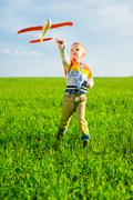 Happy boy playing with toy airplane against blue summer sky and green field Stock Photos