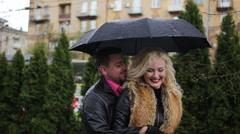 Smiling couple flirtation under the black umbrella when raining Stock Footage