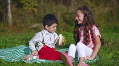 Little children eat a banana in nature Stock Footage