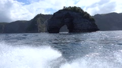Cliffs of Nusa Penida from speed boat with donut shaped rock, Bali Stock Footage