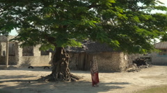 African woman under a big tree in the village Stock Footage