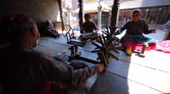 Women spin in the yard to make a string in national way. Bhaktopur, Nepal Stock Footage