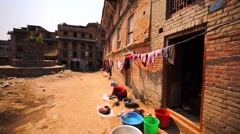 Local woman of Bhaktapur does washing loundry at street. View of drying clothes Stock Footage