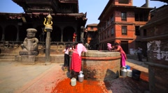 Women pull water in containers from well. Bhaktapur, Nepal Stock Footage